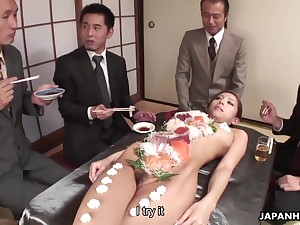 Horny businessmen are eating food off a hot babe's naked body